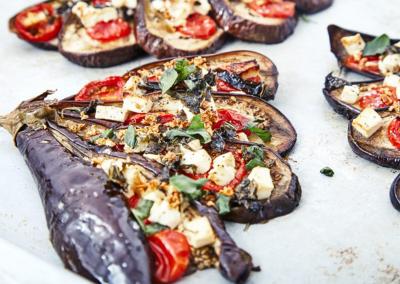 Gebakken gesneden aubergines in waaiervorm met kaas feta, tomaten, basilicum, verkruimelde noten, olijfolie