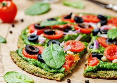 Veganistisch broccoli courgette pizzabodem met spinazie pesto tomaten ui en olijven